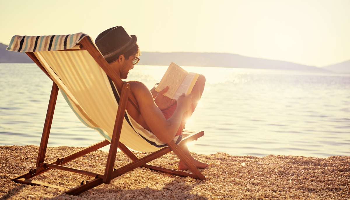 A young man reading a book while sitting on a chair at the beachhttp://195.154.178.81/DATA/i_collage/pu/shoots/805670.jpg